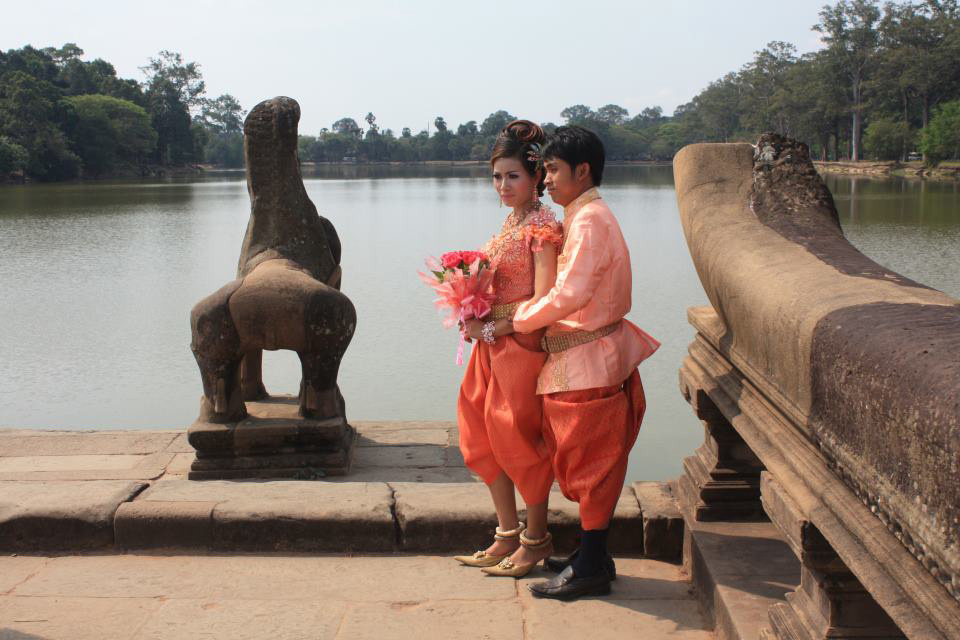 A Cambodian couple in traditional Khmer wedding dress took photograph for pre-wedding photograph at  the main causeway across the moat of Angkor Wat, Siem Reap, Cambodia.